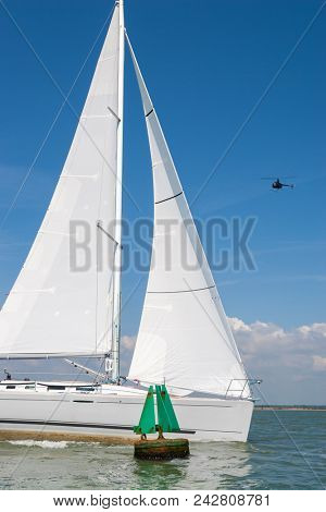 Sailing boat, sail boat or yacht with white sails passing a green navigation buoy at sea while a black helicopter flies over head