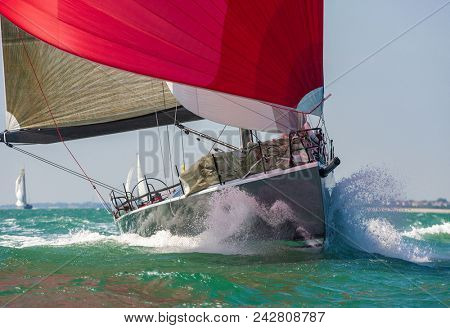 Close up of sailing boat, sail boat or yacht at sea with red sails