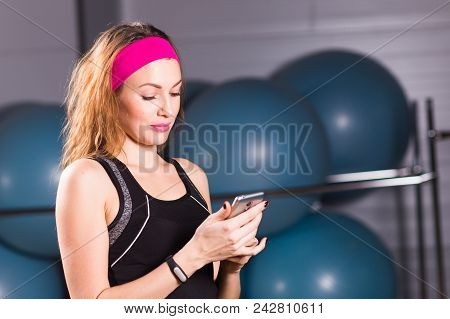 Sporty young woman with fitness tracker on color background poster