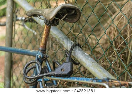 Old Bicycle Secured With A Bicycle Lock - Detail Of Bicycle Lock And Saddle