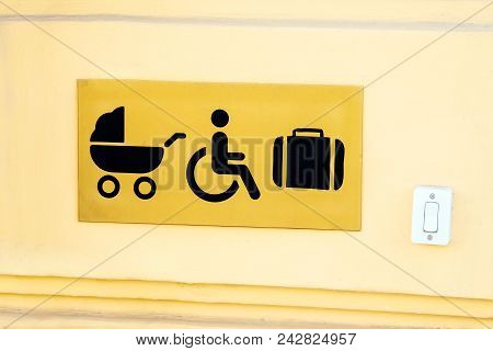Door opener button for disabled people, stroller and luggage at yellow building. Call button for personnel for lifting wheelchairs, baby carriage and luggage. poster