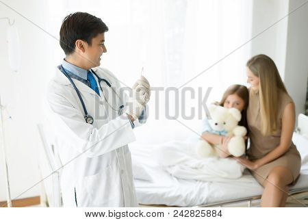 Doctor Holding A Syringe To Inject Vaccine. Background Is Mother Hugging Her Daughter Who Is A Docto