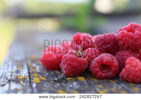 Ripe raspberry on the table in the garden. Fresh raspberry. Juicy red berries on a wooden table. Delicious and healthy food. A healthy way of life. Sweet raspberry. Jam of raspberries. Summer berry