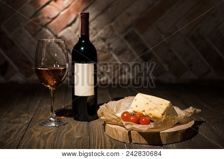 Close Up View Of Bottle And Glass Of Wine With Cheese And Cherry Tomatoes On Baking Paper On Wooden