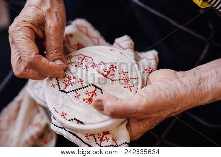 Grandmother's Hands Behind Embroidery. Fancywork With Ornament.