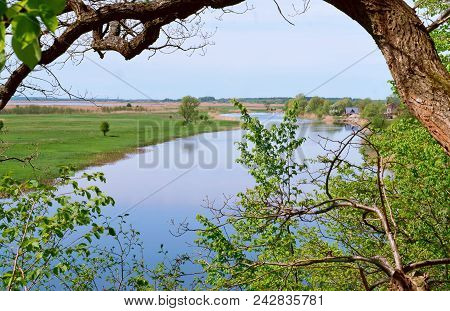 The River Landscape And The Sky Through The Trees, The River In The Distance, A Winding Blue River A