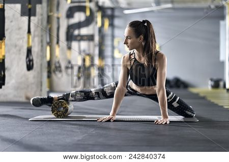 Pretty Girl Is Training With A Black-yellow Foam Roller On The Gray Mat In The Gym. She Wears A Blac