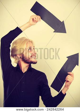 Planning, Directions, Choices Concept. Man Holding Two Black Arrows Pointing In The Same Directions.