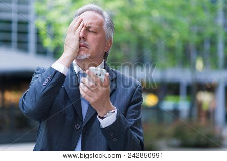 Desperate businessman holding his cell phone