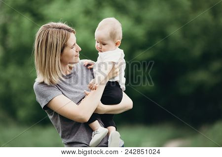 Mother Hugging Little Baby Daughter. Mom And Toddler Child Walking Outdoors. Childhood, Parenthood,