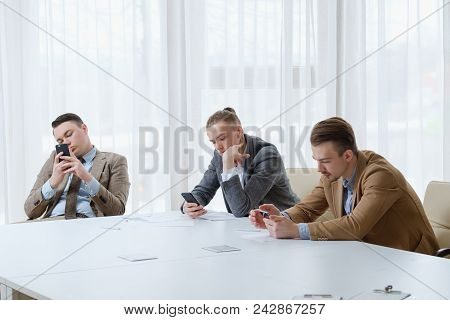 Bored Indifferent Business Men On Board Meeting Looking At Their Phones. Waiting For Boss. Idlers At