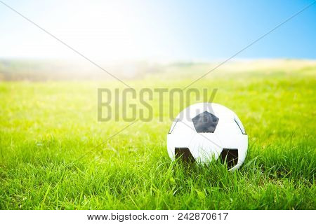 Soccer Ball Or Football Ball On Ground And Green Field Of Grass.