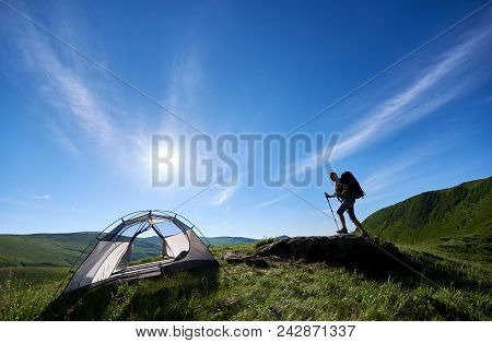 Young Woman Backpacker With Backpack And Trekking Sticks Climbing Up On Big Stone On The Top Of A Hi
