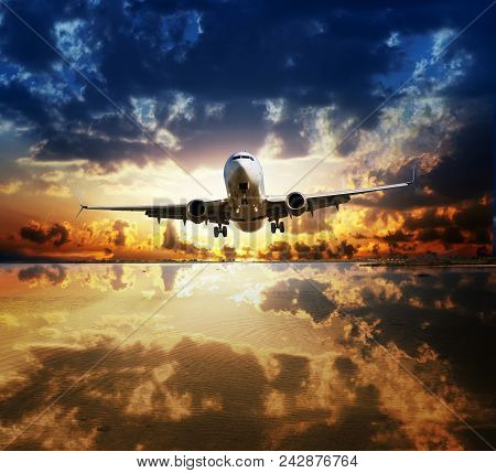 Landing Plane Flying Over Water Surface Reflecting Cloudy Sunset Sky