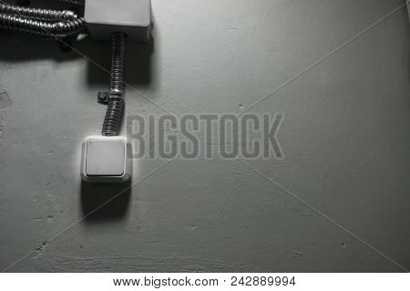 White Light Switch With An Iron Cable On A Light Wall. White Switch On Gray Concrete Wall.