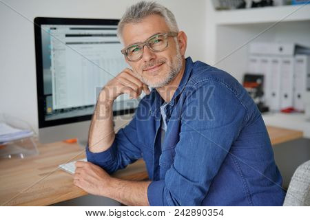 Man at home working on desktop computer