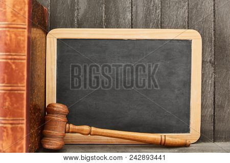Empty blackboard and judge gavel beside law book as law background