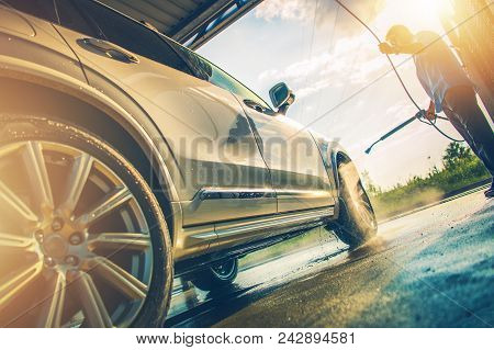 Caucasian Men In His 30s Washing Modern Vehicle Inside The Car Wash. Cleaning Using High Pressured W