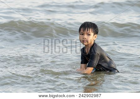 Boy Is Playing With Sand And Wave On The Beach
