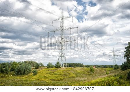Power Towers On Natural Landscape. Transmission Towers On Cloudy Sky. Electricity Pylon Structure Wi