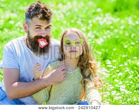 Dad And Daughter Sits On Grass At Grassplot, Green Background. Family Spend Leisure Outdoors. Child