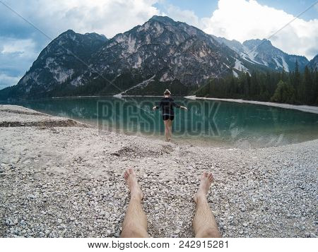 Mans Legs And Women Standing Against Amazing View Of Braies Lake Lago With Mountains Reflected In La