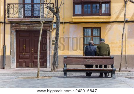 Leon, Spain - April 16, 2018: Two Older Men Leaning Against A Bench In Leon, Spain
