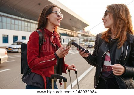 Photo of two excited european women traveling abroad and using mobile phones while waiting for flight or after departure standing with luggage near airport. Air travel concept
