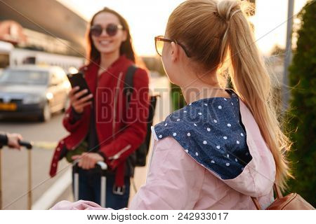 Photo of two young women traveling abroad together, and using mobile phone while waiting for flight with luggage near airport. Air travel or holiday concept