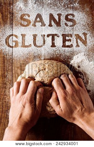 high-angle shot of a young man kneading a piece of dough on a wooden table sprinkled with a gluten free flour where you can read the text sans gluten, gluten free written in french