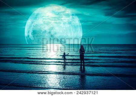 Super Moon. Colorful Sky With Bright Full Moon Over Seascape. Silhouette Of Mother With Her Child Pl