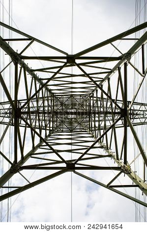 Transmission Tower Bottom View. Power Tower On Cloudy Sky. Electricity Pylon Structure For Power Lin