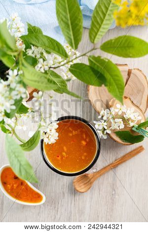 Vitaminic Healthy Sea Buckthorn Tea In Metal Tea Cup On The White Background. Blooming Tree Branches