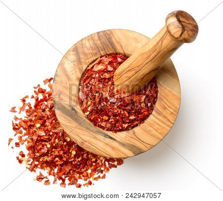 Dried Red Chilli Flakes In The Wooden Mortar, Isolated On White Background