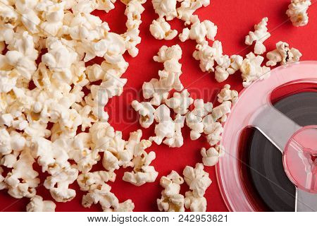 Movie Background. Popcorn And Film Reel On Red Backdrop. Entertainment And Cinematography Concept