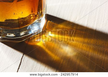 Whiskey In Glass, Ice Cub Served In A Short Glass On White Wooden Table