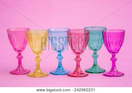 Row Of Multi Colored Glasses On Pink Background