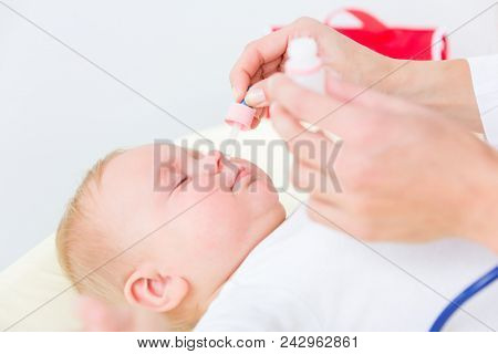 Close-up of the hands of a pediatrician clearing the nose of a baby, by applying saline solution in the nostrils with a nasal aspirator during physical check-up