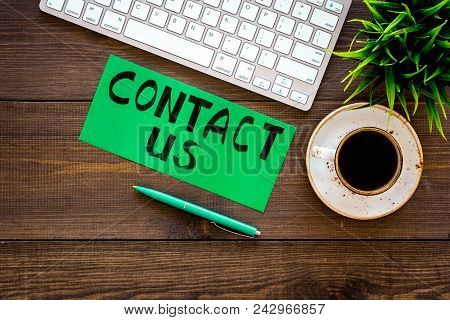 Frame Contact Us. Lettering Contact Us On Office Work Desk With Computer On Dark Wooden Background T