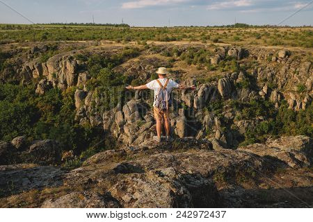 Stylish Young Man With Beard Standing On The Precipice Of The Canyon
