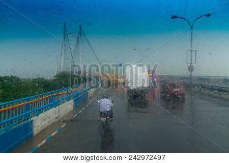 Vidyasagar Setu (Bridge) over river Ganges, known as 2nd Hooghly Bridge in Kolkata,West Bengal, India. Abstract image shot aginst glass with raindrops all over it, monsoon image of Kolkata. poster