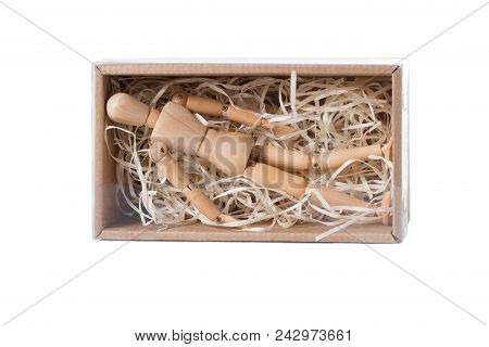 Wooden Mannikin Lying In Closed Cardboard Box Filled With Wood Shred. Concept Of Loneliness, Isolati