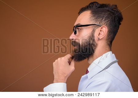 Studio Shot Of Young Handsome Bearded Persian Man Doctor Against Brown Background