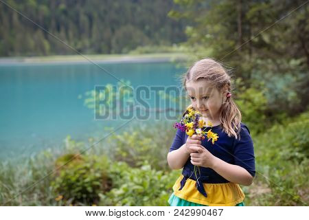 Child Hiking In Flower Field At Mountain Lake
