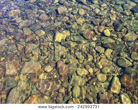Clear Water Of A Mountain River. Sun Glare On River Stones Under Clear Water.