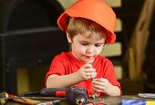 Child in hard hat, helmet playing with hex bolts as builder or repairer, handcrafting. Toddler on busy face plays with bolts at home in workshop. Handcrafting concept. Kid boy play as handyman. poster