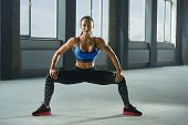 Frontview of attractive woman with athletic body doing sitting up and downs in spacy gym. Having sturdy muscles, healthy body and tanned skin. Looking strong, fit, feeling good. Wearing sportswear. poster