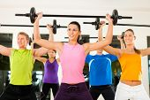 Group of five people exercising using barbells in gym or fitness club to gain strength and fitness poster