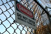 danger do not enter sign on fence topped with barbed wire poster