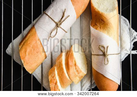 Sliced French Baguette With Crumbs On Dark Background
